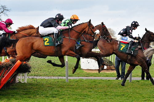 Horses jump a fence at Aintree