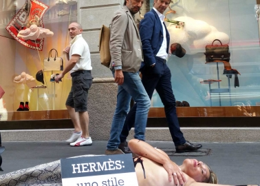 PETA supporters poses as reptile outside Hermes store in Italy